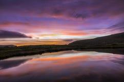 Una puesta del sol colorida reflejó en un lago con las nubes rojas y el cielo azul (Faroe Island) Imagenes de archivo