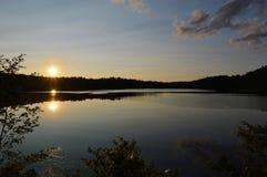 Una puesta del sol de la caída da vuelta a un lago en un espejo Fotografía de archivo
