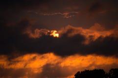 Una puesta del sol dramática detrás de las nubes Foto de archivo