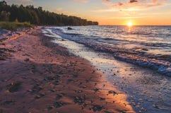 Una puesta del sol en una playa imagen de archivo libre de regalías