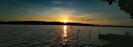 Una puesta del sol en un mar con un barco Foto de archivo
