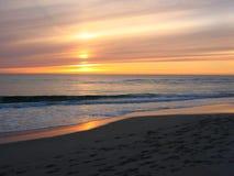 Una puesta del sol en una playa Fotografía de archivo libre de regalías