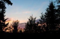 Una puesta del sol es los sun's se besa ardientemente a la noche, dos líneas blancas de los aviones del vuelo imágenes de archivo libres de regalías