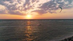 Una puesta del sol hermosa en el mar, un kiter que flota más allá de la playa que controla una cometa del entrenamiento almacen de video