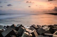 Una puesta del sol hermosa en la playa del glagah, con la roca-fractura de las ondas en progo del kulon, Yogyakarta, Indonesia, A fotografía de archivo