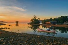 Una puesta del sol hermosa pero el trastornar causó por la playa que es contaminado por el plástico que la gente ha lanzado a su  foto de archivo