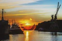 Una puesta del sol hermosa sobre las naves del puerto de Letonia Imagen de archivo libre de regalías