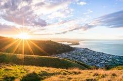 Una puesta del sol llamativa de una ciudad montañosa hermosa de la playa imagenes de archivo