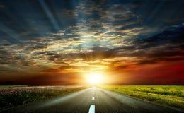 Una puesta del sol maravillosa y un camino pavimentado imagenes de archivo