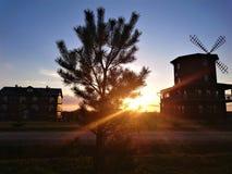 Una puesta del sol pintoresca contra un cielo azul, casas y un molino fotos de archivo