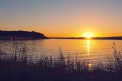 Una puesta del sol sobre un lago de la montaña Fotos de archivo