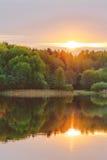 Una puesta del sol tranquila en la orilla del lago, en donde el bosque refleja en agua tranquila con neblina y niebla Imágenes de archivo libres de regalías