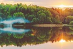 Una puesta del sol tranquila en la orilla del lago, en donde el bosque refleja en agua tranquila con neblina y niebla Fotos de archivo