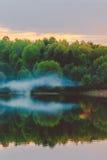 Una puesta del sol tranquila en la orilla del lago, en donde el bosque refleja en agua tranquila con neblina y niebla Foto de archivo libre de regalías