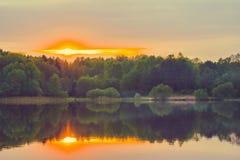 Una puesta del sol tranquila en la orilla del lago, en donde el bosque refleja en agua tranquila con niebla Imágenes de archivo libres de regalías