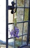 Una puntilla de la lavanda colgó al revés para secarse en la manija de una ventana fuera de una casa medieval tradicional del est Imágenes de archivo libres de regalías