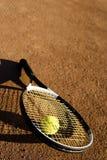 Una racchetta e una sfera di tennis Immagine Stock