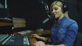Una radio DJ lee noticias en el estudio de difusión almacen de metraje de vídeo