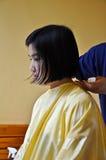 Una ragazza è capelli di taglio Immagine Stock