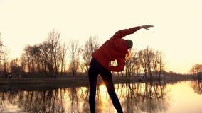 Una ragazza è impegnata negli esercizi relativi alla ginnastica al tramonto sulle banche del fiume nel parco della città Isolato  archivi video