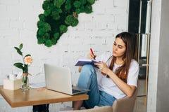 Una ragazza è le free lance che si siedono in un caffè con un taccuino e scrive le note in un taccuino Fotografie Stock