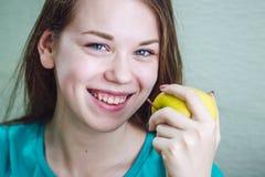 Una ragazza è sorridente e tenente una mela in sua mano Immagini Stock