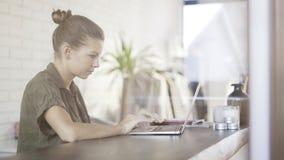 Una ragazza abbastanza seria dei giovani con un computer portatile che si siede ad una tavola Fotografie Stock
