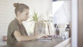 Una ragazza abbastanza seria dei giovani con un computer portatile che si siede ad una tavola Immagine Stock