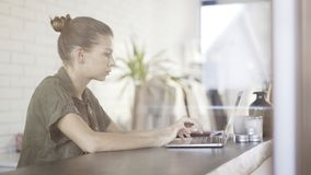 Una ragazza abbastanza seria dei giovani con un computer portatile che si siede ad una tavola Immagine Stock Libera da Diritti