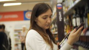 Una ragazza in abbigliamento casual sceglie il vino in un supermercato Tiene una bottiglia di vino dallo scaffale nel deposito archivi video