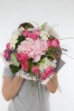 Una ragazza in abbigliamento casuale sta tenendo un mazzo dei fiori Nessun fronte unrecognisable Fotografie Stock