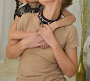 Una ragazza abbraccia una donna da dietro, un albero di Natale dietro loro la figlia abbraccia sua madre da dietro, festa, nuovo  fotografia stock libera da diritti