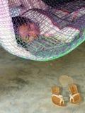 Una ragazza addormentata in Hamaca e nell'impatto di povertà sulle povere vicinanze in America Centrale Immagini Stock
