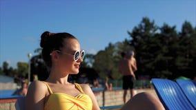 Una ragazza adulta che prende il sole vicino ad una piscina all'aperto su un lettino della spiaggia stock footage
