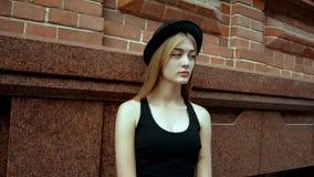 Una ragazza affascinante in una maglietta ed in un cappello neri archivi video