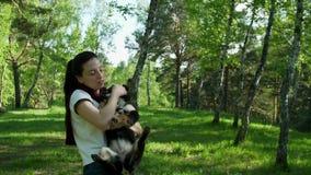 Una ragazza afferra un cane e lo tiene lei armi stock footage