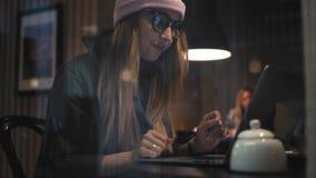 Una ragazza alla moda dei pantaloni a vita bassa in vetri che scrive su un computer portatile Vista attraverso la finestra archivi video