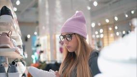 Una ragazza alla moda dei pantaloni a vita bassa viene allo scaffale del negozio di scarpe e sceglie le nuove scarpe da tennis Fotografia Stock