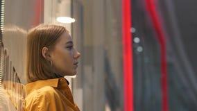 Una ragazza alla moda dell'adolescente sui precedenti di una vetrina di vetro brillante stock footage