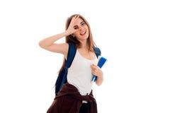 Una ragazza allegra in maglietta e con uno zaino sull'occhio della spalla chiude la mano Fotografie Stock