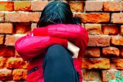 Una ragazza, 13 anni, della corsa europea, in un rivestimento rosso contro un muro di mattoni, ha nascosto il suo fronte con le s fotografia stock