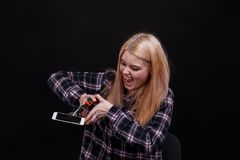 Una ragazza arrabbiata, rotture uno smartphone per mezzo di una clip della costruzione Su un fondo nero immagine stock