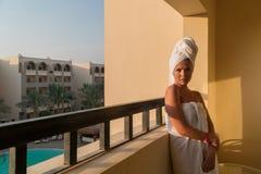 Una ragazza in asciugamani bianchi è emerso appena dal bagno e dai supporti sul balcone della camera di albergo immagini stock