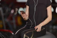 Una ragazza ascolta la musica in una palestra immagine stock libera da diritti