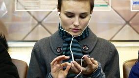 Una ragazza ascolta musica o guarda il video su uno smartphone in un'automobile di sottopassaggio video d archivio