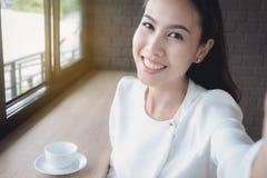 Una ragazza asiatica sta prendendo la sua propria immagine durante una pausa caffè du immagine stock