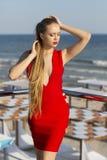 Una ragazza attraente che posa su un terrazzo su un fondo blu del mare Una signora in un vestito rosso luminoso Una donna con cap Immagine Stock Libera da Diritti