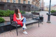 Una ragazza attraente con capelli marroni lunghi e un sorriso bianco del dente si siede su un banco e le scrive i pensieri sui pr Immagini Stock