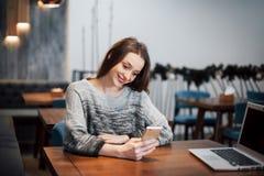 Una ragazza attraente con capelli neri lunghi riflette un nuovo progetto durante una pausa caffè che si siede ad una tavola in un Fotografia Stock