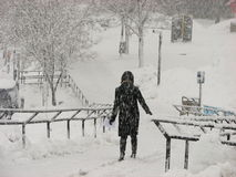 Una ragazza in attrezzatura nera nella tempesta della neve pesante a UWM Fotografie Stock Libere da Diritti